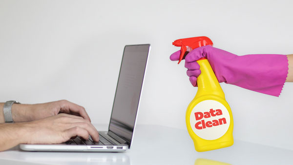 Spray bottle labeled Data Clean pointed at laptop