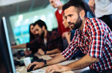 Computer programmer sitting at desktop workstation