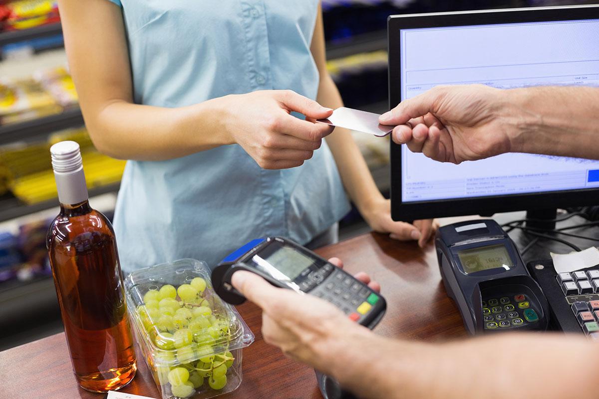Woman handing credit card to POS vendor