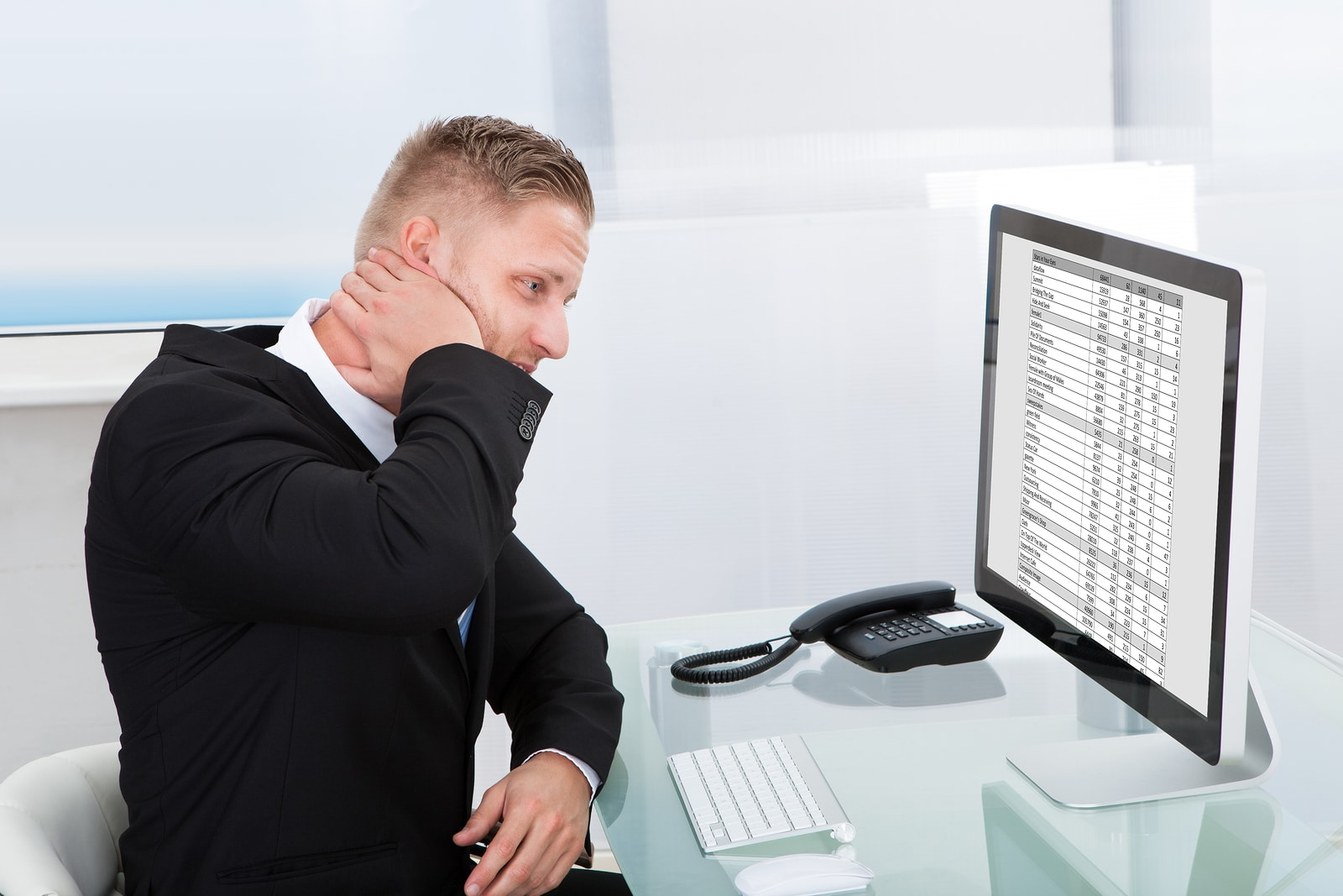 Man overwhelmed by spreadsheets