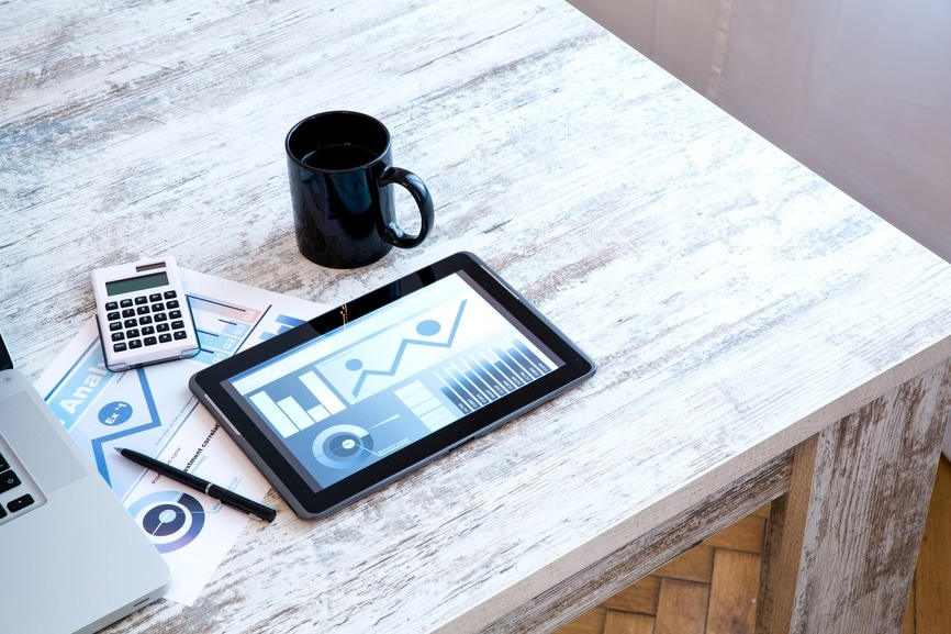 Tablet showing Enterprise Performance Management Tools, with calculator and coffee mug on table